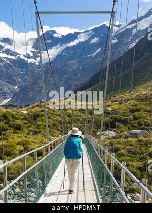 Aoraki/Mount Cook National Park, Canterbury, New Zealand. Hiker on the Hooker Valley Track crossing suspension bridge - Stock Photo