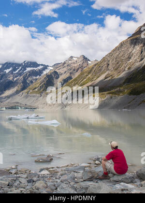 Aoraki/Mount Cook National Park, Canterbury, New Zealand. Hiker on the rocky shore of Hooker Lake, terminus of the - Stock Photo