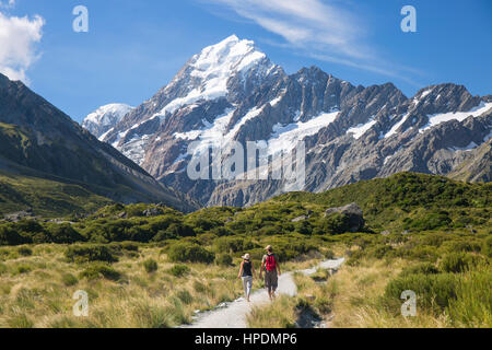Aoraki/Mount Cook National Park, Canterbury, New Zealand. Hikers on the Hooker Valley Track heading towards snow - Stock Photo