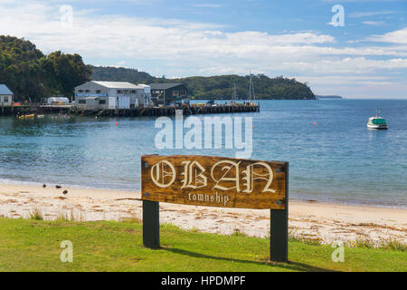 Oban, Stewart Island, Southland, New Zealand. Carved wooden sign on the shore of Halfmoon Bay. - Stock Photo