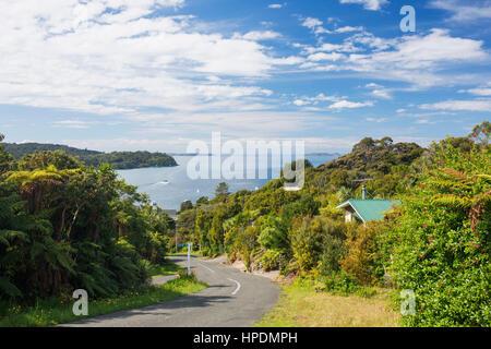 Oban, Stewart Island, Southland, New Zealand. View down steep hill to Halfmoon Bay. - Stock Photo