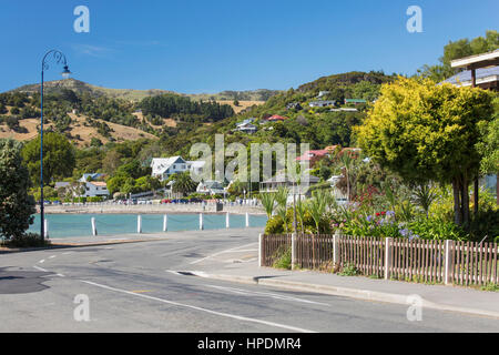 Akaroa, Canterbury, New Zealand. View along Beach Road to Akaroa Harbour. - Stock Photo
