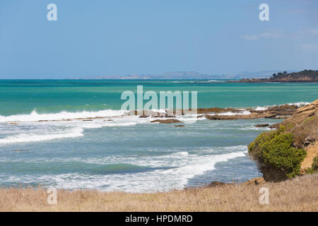 Oamaru, Otago, New Zealand. View across the turquoise waters of the Pacific Ocean from rocky coastline near Kakanui. - Stock Photo