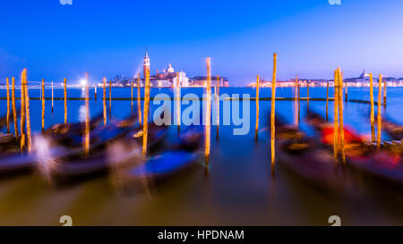 gondolas line the bank at st mark's square in venice during blue hour. The image is a long exposure causing the gondolas to become blurred and illustr