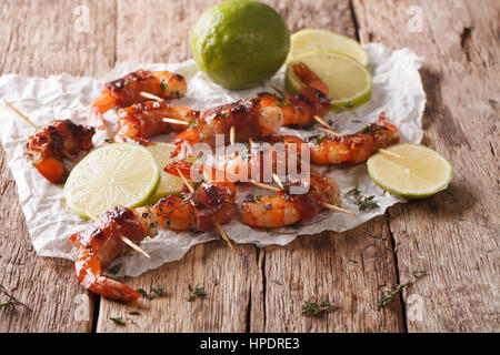 Tiger prawns wrapped in bacon on skewers with thyme and lime close up on the table. Horizontal - Stock Photo
