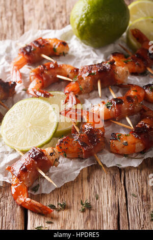 Tiger prawns wrapped in bacon on skewers with thyme and lime close up on the table. vertical - Stock Photo