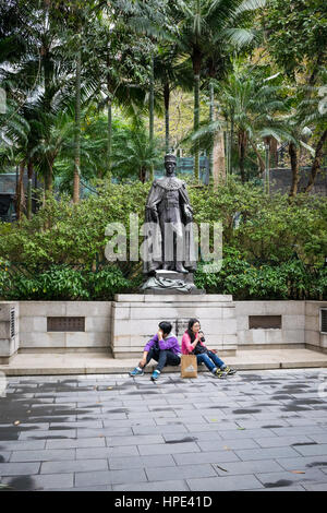 Tired tourists resting in front of bronze statue of King George VI at Hong Kong zoo (Zoological and Botanical Gardens) - Stock Photo