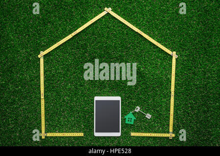 Real estate and renovation concept: folding meter composing a house shape with tablet as door and house keys on - Stock Photo