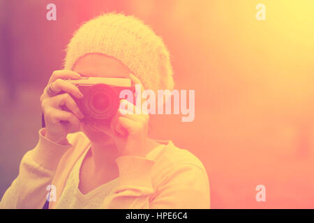 Woman with retro camera in sunset - Stock Photo