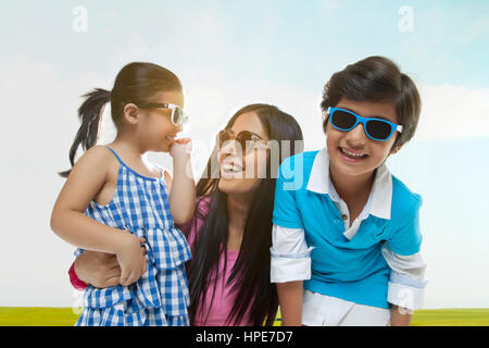 Smiling family wearing sunglasses having fun in a park on sunny day - Stock Photo