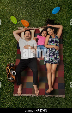 Couple and young daughter lying on picnic blanket - Stock Photo