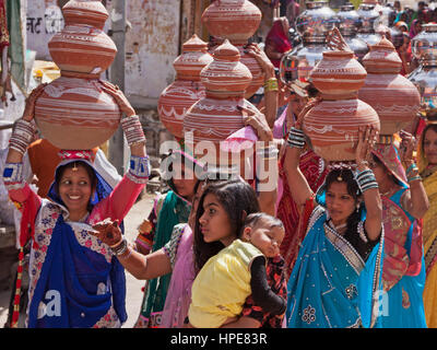 Women bearing symbolic bowls on their heads in a procession making its way through the streets of Deogarh in rajasthan - Stock Photo