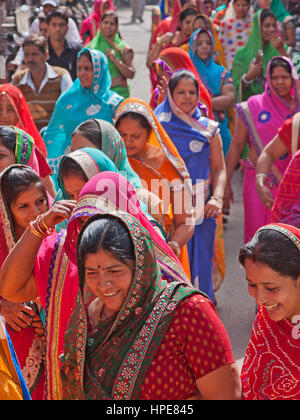Women in a procession making its way through the streets of Deogarh in Rajasthan, India, as part of wedding celebrations - Stock Photo