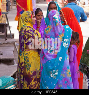 Women in typically colorful Rajasthani dress engaged in conversation in the crowded market area of Deogarh town - Stock Photo