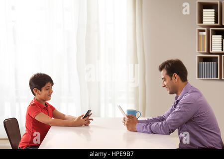 Father and son using mobile phones sitting on dining table - Stock Photo