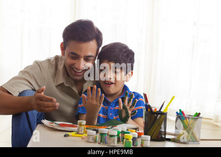 Smiling father and son finger painting together - Stock Photo