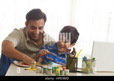 Father and son finger painting together - Stock Photo
