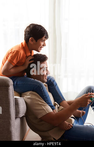 Father and son sitting on sofa playing video game - Stock Photo