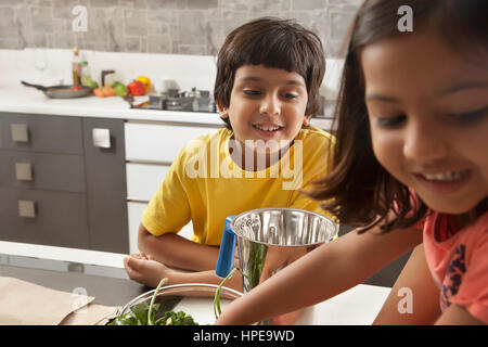 Brother and sister having fun together in kitchen - Stock Photo