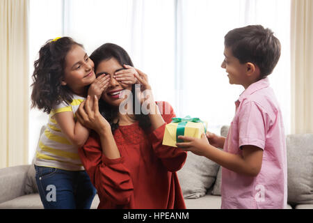 Young daughter closing eyes and son presenting gift to their mother - Stock Photo