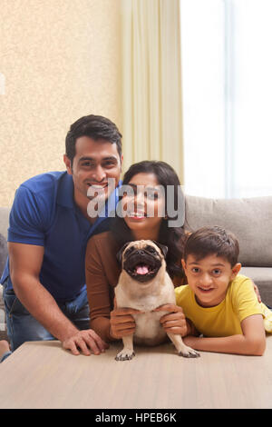 Portrait of smiling family with son and pug - Stock Photo
