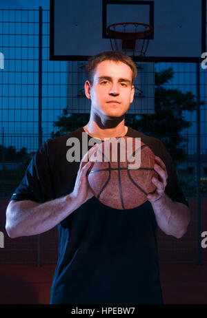 Frontal torso view of a basketball player in the flare with basketball held on in the evening. - Stock Photo
