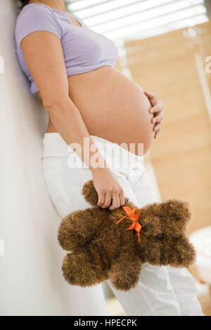 Model released , Schwangere Frau mit Teddybaer in der Hand - pregnant woman with teddy bear - Stock Photo