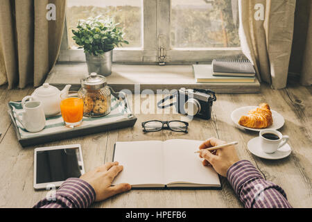 hipster having coffee and writing in planner stock photo, royalty