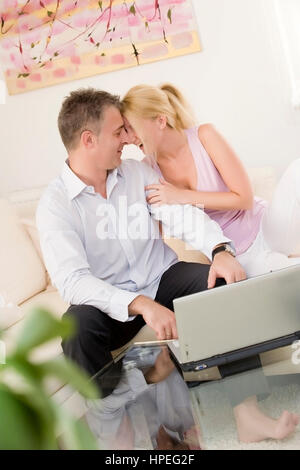 Model released , Lachendes Paar sitzt mit Laptop auf Couch im Wohnraum - lucky couple using laptop - Stock Photo
