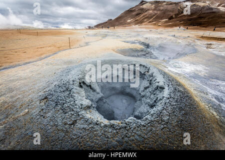 Hverir, geothermal area in Northern Iceland, with steam and mud pools. tourists enjoying the view - Stock Photo