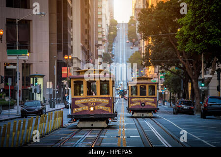 Classic view of historic traditional Cable Cars riding on famous California Street in beautiful morning light at - Stock Photo