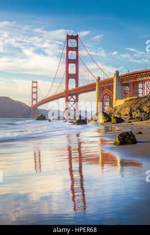 Classic vertical view of famous Golden Gate Bridge seen from scenic Baker Beach in beautiful golden evening light - Stock Photo