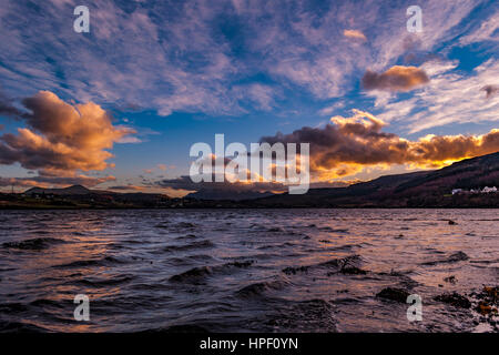 Cuillin Hills Mountain Range, across Loch Portree, on the Isle of Skye, Scotland, against a dramatic sky, late February - Stock Photo