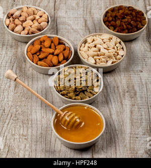 Pistachios, almonds, peanuts, pumpkin seeds, raisins and honey in ceramic plates. On the wooden table. Healthy eating - Stock Photo