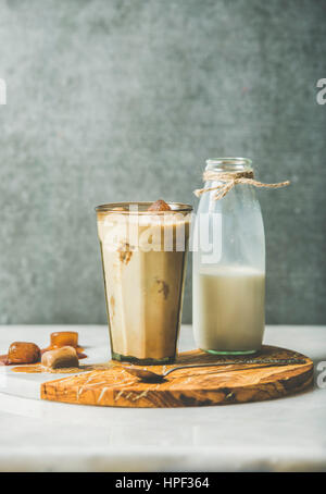 Iced caramel latte summer coffee cocktail with milk and frozen coffee ice cubes in glass on serving olive wood and - Stock Photo