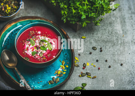 Spring detox beetroot soup with mint, chia, flax and pumpkin seeds on bright blue ceramic plate over grey concrete - Stock Photo
