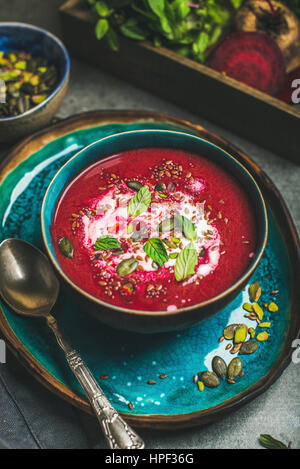 Spring detox red beetroot soup with mint, chia, flax and pumpkin seeds in blue ceramic bowl over grey concrete background. - Stock Photo
