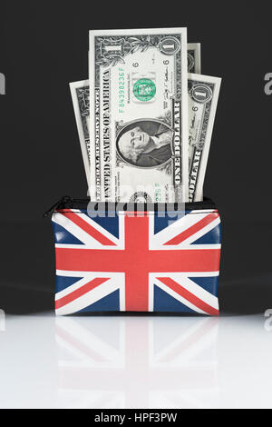 Union Jack coin purse with US Dollars ... set against a dark background. As metaphor for US Dollar-Sterling exchange - Stock Photo