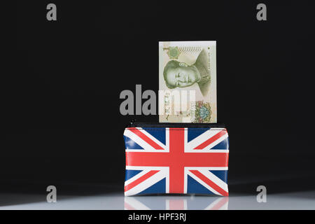 Union Jack coin purse with Chinese Yuan / Renminbi ... against a dark background. Metaphor for Yuan-Pound exchange - Stock Photo