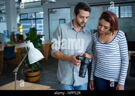 Man and woman reviewing photographs on digital camera  in creative office - Stock Photo