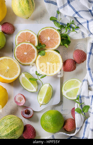 Variety of whole and sliced citrus fruits pink tiger lemon, lemon, lime, mint and exotic lichee on white chopping - Stock Photo
