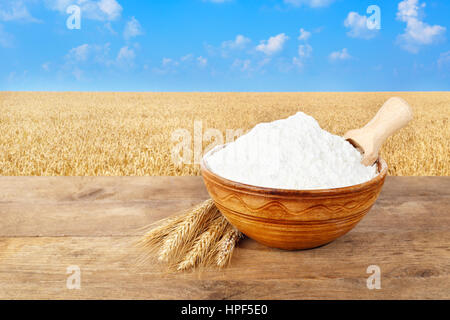 wheat flour in ceramic bowl. Ears of wheat and wheat flour in bowl on table with field of wheat on the  background. - Stock Photo