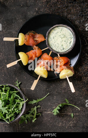 Delicious Appetizer with smoked salted salmon and boiled potatoes on skewers served with creamy dill sauce and arugula - Stock Photo