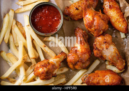 Fast food fried spicy chicken legs, wings and french fries potatoes with salt and ketchup sauce served on baking - Stock Photo