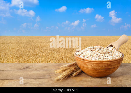 Oat flakes in bowl. Ears of oats and oatmeal in bowl on table with field on the background. Golden field and blue - Stock Photo