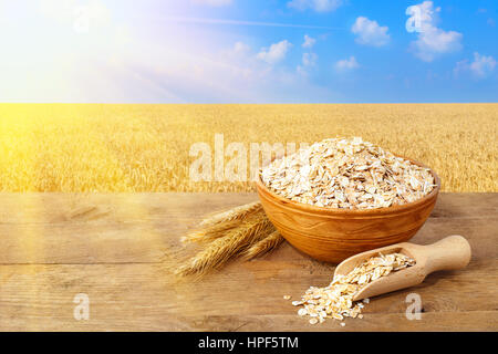 Oat flakes in bowl. Ears of oats and oatmeal in bowl on table with field with sunshine on the background. Agriculture - Stock Photo
