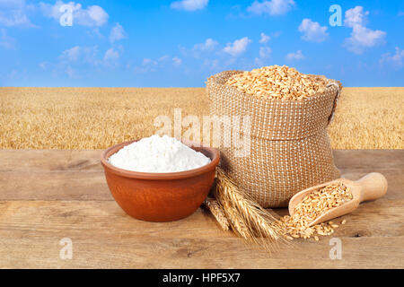wheat grains in sack. Ears of wheat and wheat grains in bag and flour in bowl on table with field of wheat on the - Stock Photo