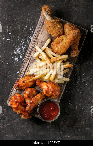 Fast food fried crispy and spicy chicken legs, wings and french fries potatoes with salt and ketchup sauce served - Stock Photo