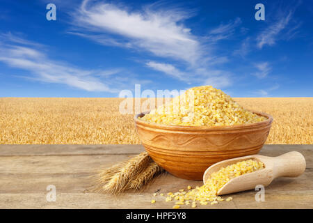 Bulgur or couscous in bowl. Bulgur in ceramic bowl and ears of wheat on table with field of wheat on the background. - Stock Photo