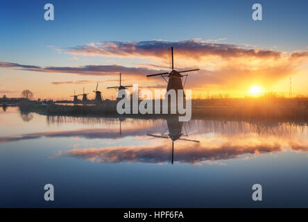 Silhouette of windmills at amazing foggy sunrise in Kinderdijk, Netherlands. Rustic landscape with dutch windmills - Stock Photo